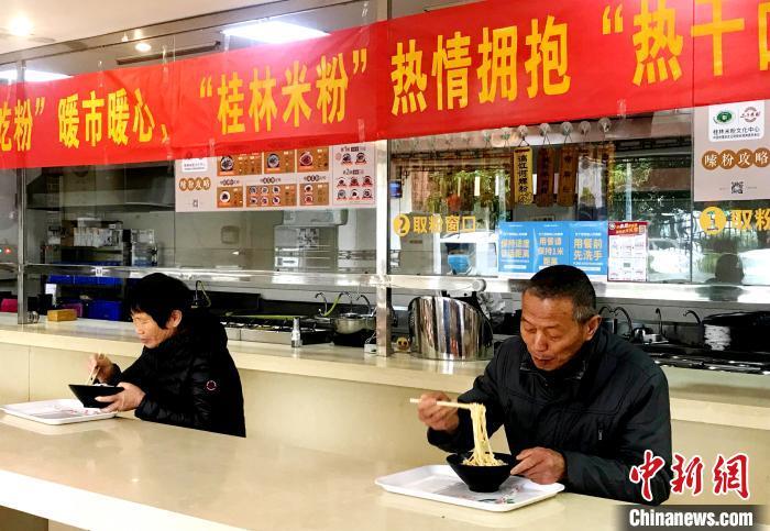 3月30日,湖北籍人员在广西桂林市七星区桂林米粉文化中心品尝桂林米粉。 王亚东 摄